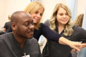 Deb Myers, Director of the sonography program, instructs Wetare and another student.