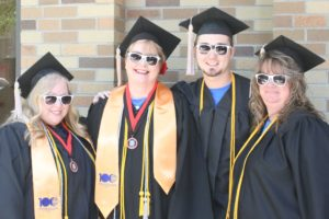 A group of graduates stands outside the Marion Palace Theatre for graduation. They are wearing MTC sunglasses.