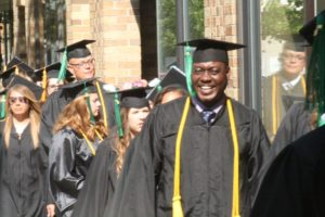 An honors student smiles outside the 2018 graduation.