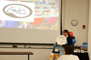 Pia Douglas presents samples of the crafts for the Art Center.