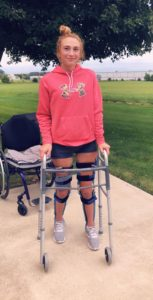 Carson standing with leg braces and a walker.