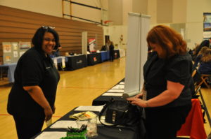 A participant smiles as she visits an employer's table.