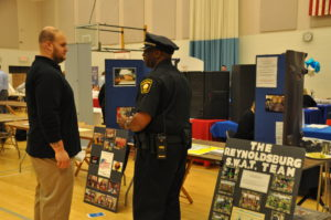 A member of the Reynoldsburg SWAT team talks to another participant at the job fair.