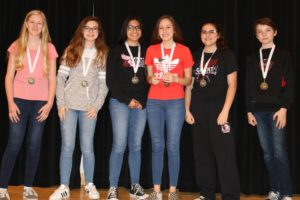 The third place team wears their ribbons and holds a trophy.
