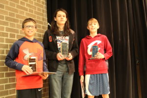 The 6th grade winners hold their trophies.