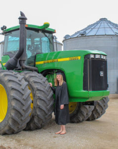 Jena Baum poses next to a John Deere tractor