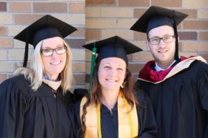 Faculty member Lori Makilagi, left; Carrie Pilierio, student speaker, center; and Josh Line, Director of the Occupational Therapy Assistant Program stand and smile at graduation.