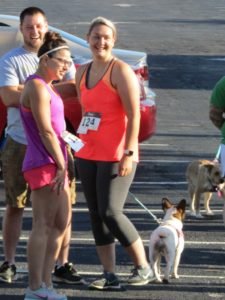 Two participants and a dog prepare for the 5K to start.