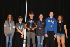 Members of the top math team wear their ribbons and hold their trophy.