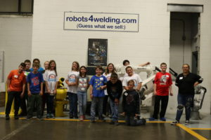 The group poses in front of a robot arm at RobotWorx.