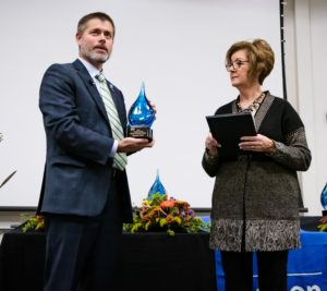 Dr. Ryan McCall hands the Alumni Hall of Fame award to inductee Pat Case.