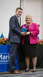 Dr. Ryan McCall hands the award to Terri Martin