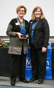 Pat Case holds her award while her nominator smiles.