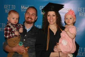 A graduate and her partner and children smile.