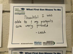 A sign reads: What First Gen means to me: Thankful I was able to & my parents are very proud! -Leah
