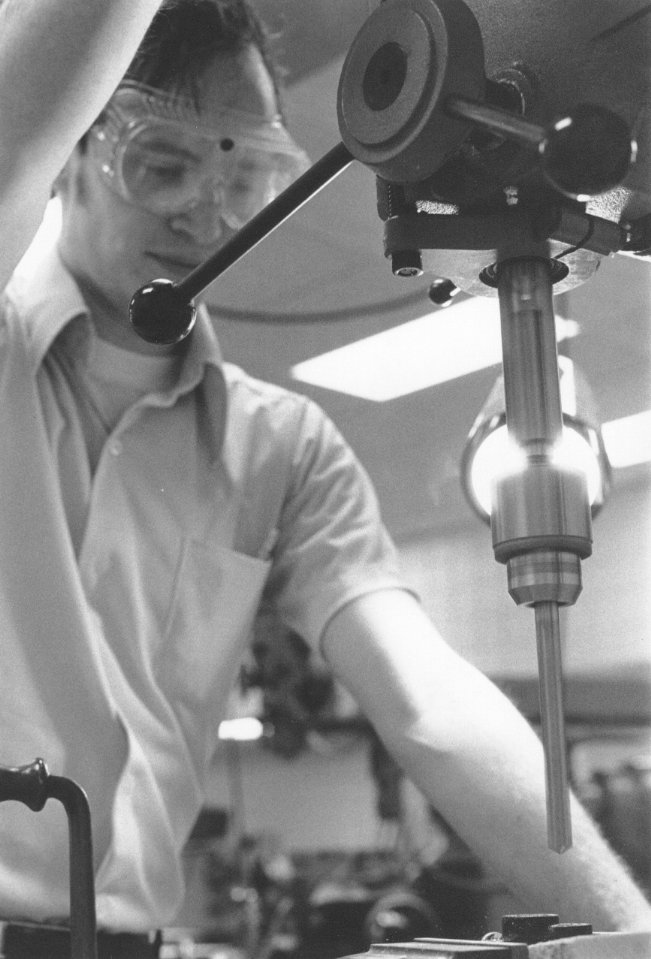 A student works in the engineering lab while wearing googles.