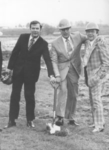 Three men hold a shovel to break ground for a new building