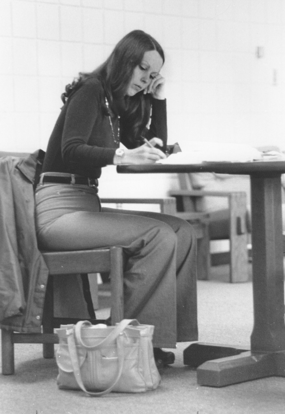 A student studies at a desk in the 1970's.