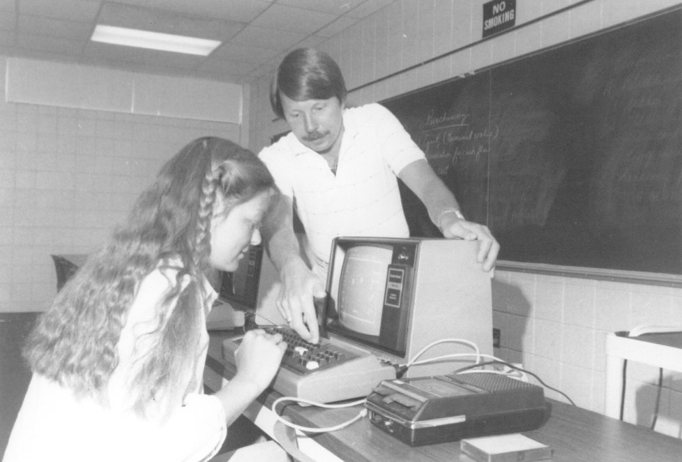 Historical photo of a student and instructor working on an early computer.