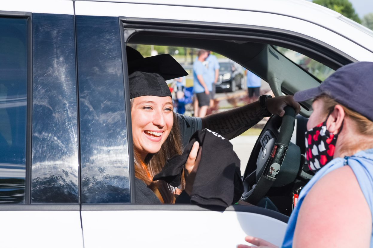 A students miles from the passenger seat while being handed her diploma.
