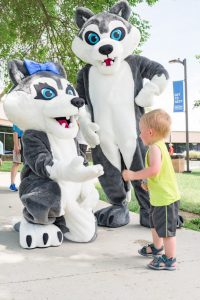 A child interacts with the two Leader mascots, which are giant Husky dogs.