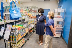 Primrose Igonor shows Dr. Lori Barr the shelves stocked with canned goods available for students in the food pantry of the Connections Center.